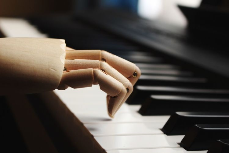 Cropped image of wooden statue on piano keys