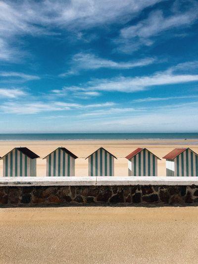 Beach houses on sand against sky