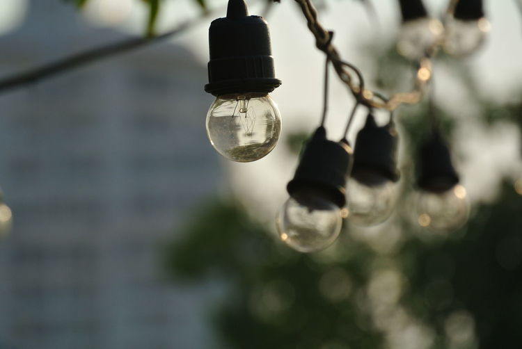 Low angle view of light bulb hanging against blurred background