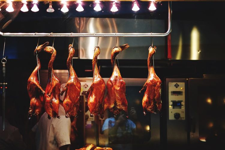 Close-Up Of Chicken Hanging In Kitchen At Night