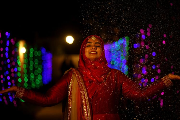 Woman standing against colorful illuminated lights at night