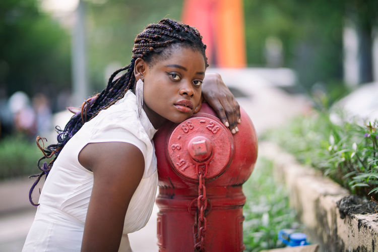 Portrait of young woman by fire hydrant in city