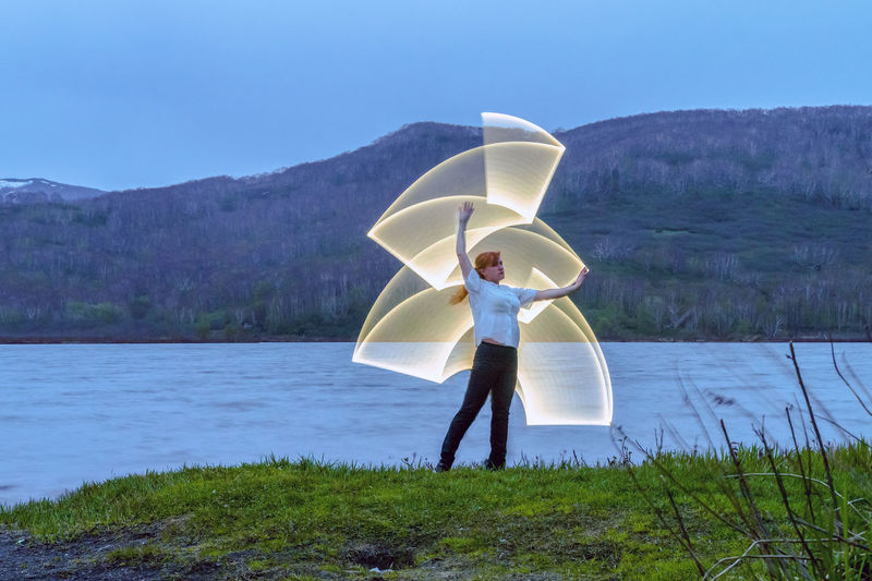 Woman Making Lighting Paintings By Lake