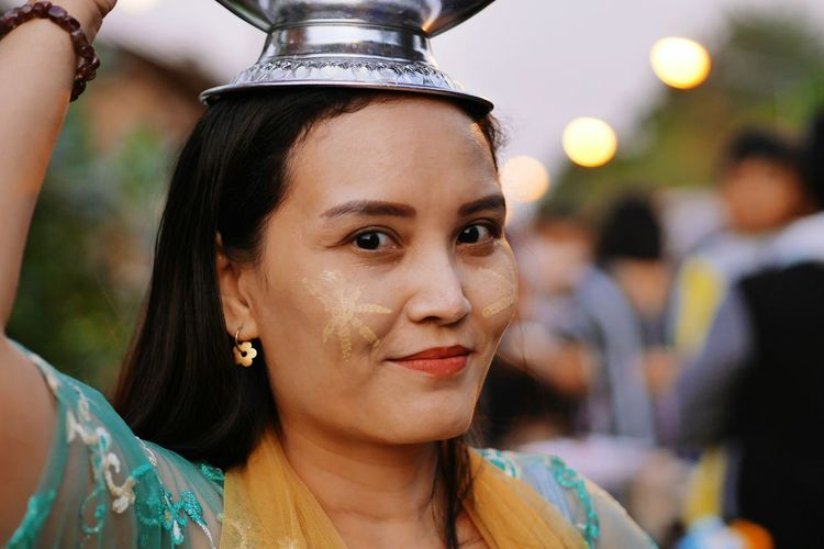 Portrait of smiling woman with face paint carrying containers on head during event