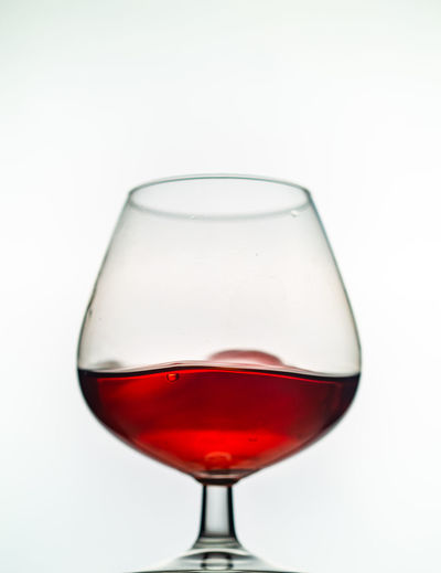 Close-up of red wineglass against white background
