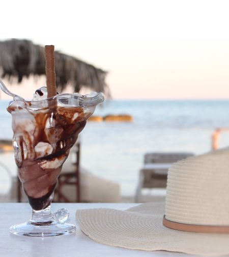 Close-up of dessert on table at beach against sky