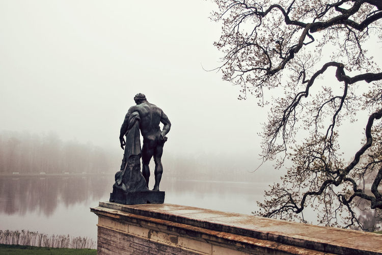 Statues against lake during foggy weather