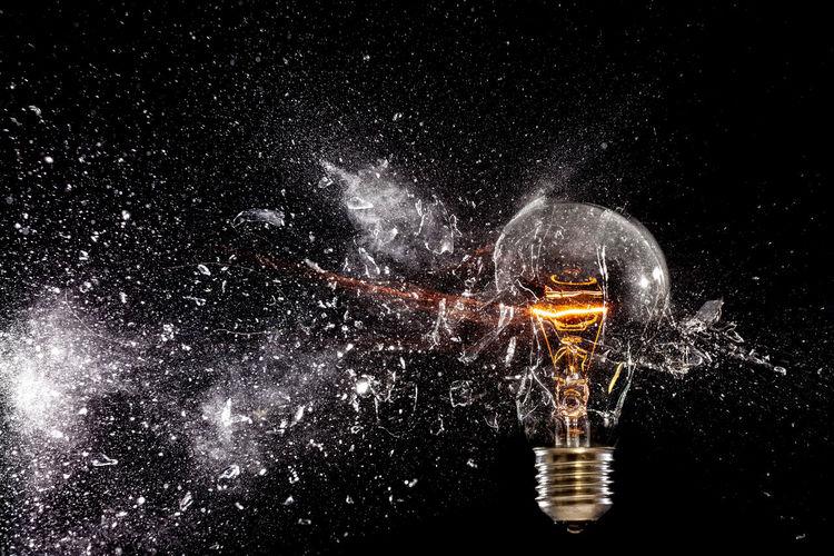 Broken illuminated light bulb against black background