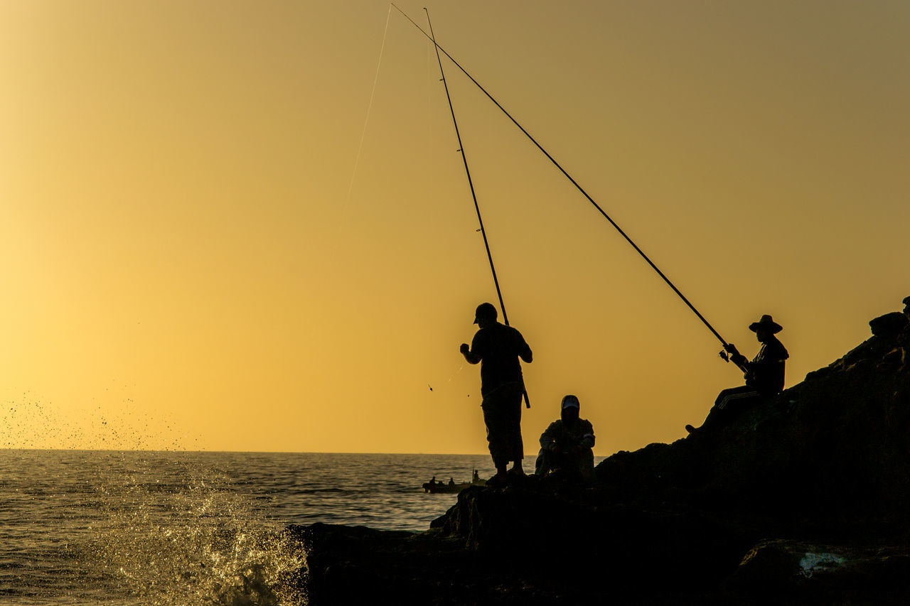 Men Fishing At Sea Against Sky During Sunset