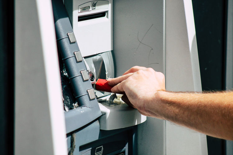 Cropped hand of man breaking atm machine