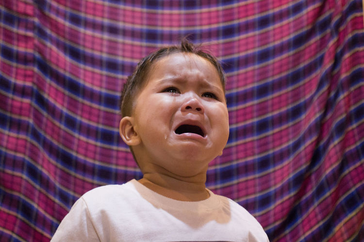 Close-up of boy crying against curtain