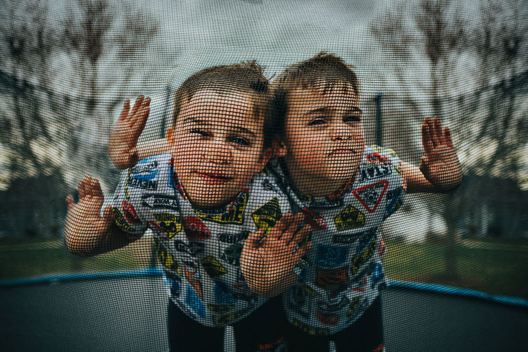 Twin boys being silly on trampoline