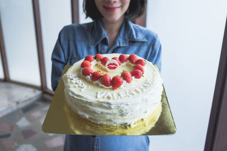 Midsection Of Young Woman Holding Valentine Cake At Home