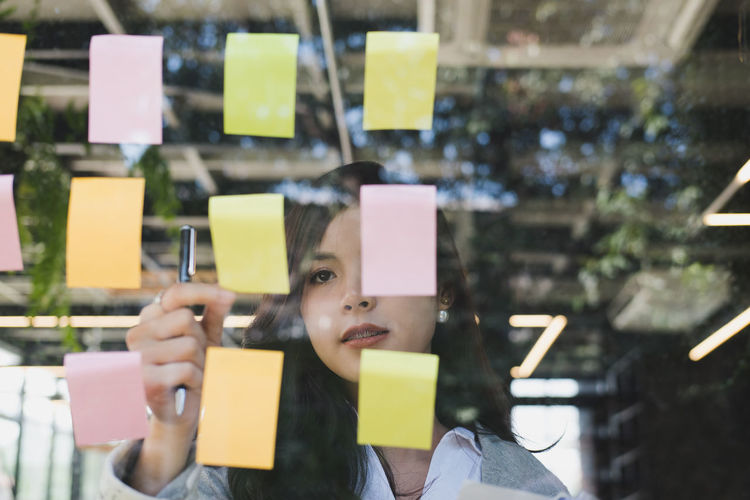 Young woman holding yellow adhesive note on glass