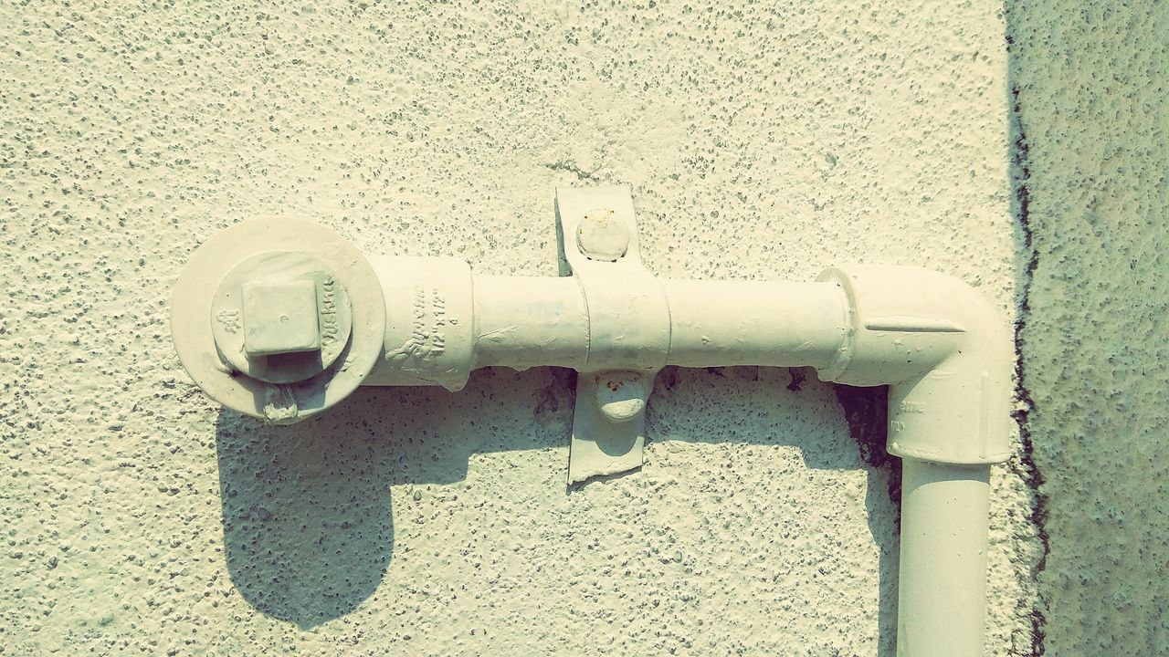CLOSE-UP OF METAL PIPE ON WALL