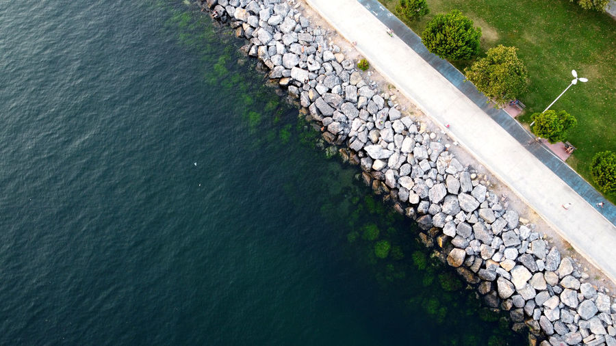 High angle view of stone wall by sea