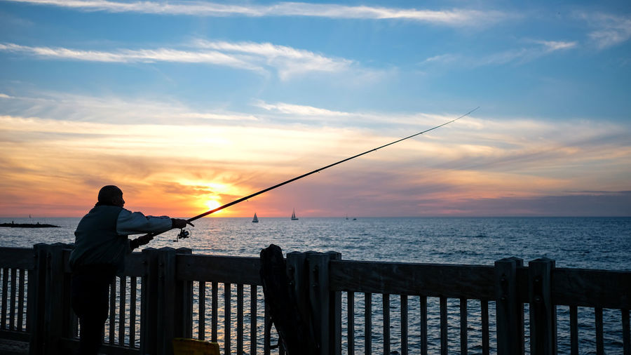 Man fishing by sea against sky during sunset