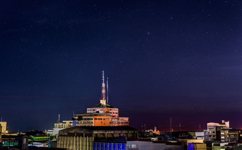 Communications tower on building against starry sky