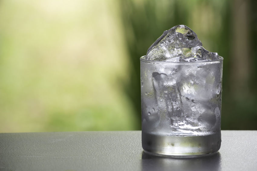 Ice cube in the glass on table with nature background Focus On Foreground Cold Temperature Food And Drink Close-up Household Equipment Glass No People Table Drink Water Transparent Drinking Glass Refreshment Frozen Drinking Water Ice Cube Ice Glass - Material Still Life Purity Non-alcoholic Beverage