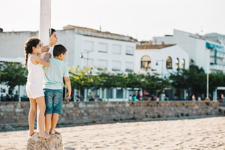 Kids standing by pole against the sky