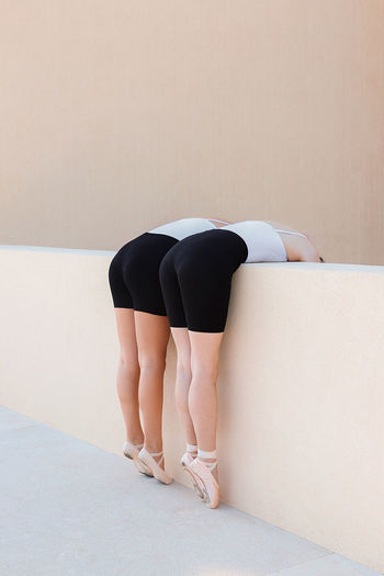 Rear view low section of woman standing against wall