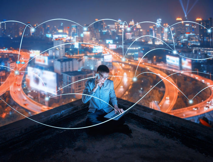 Rear view of boy sitting on illuminated cityscape at night