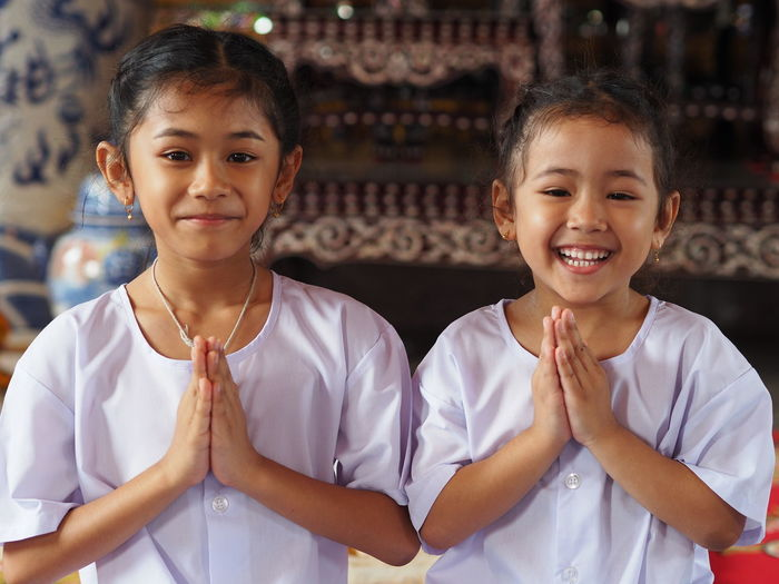 Portrait of smiling sisters in praying position standing in temple