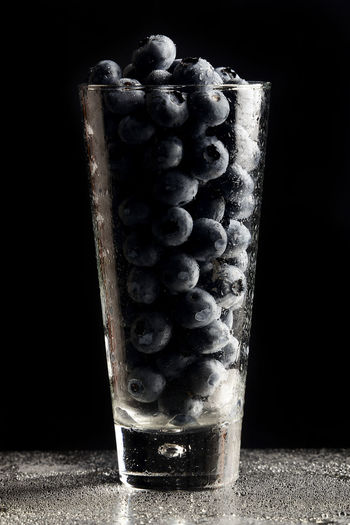 Close-up of old glass on table against black background