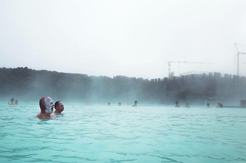 People swimming in pool against clear sky