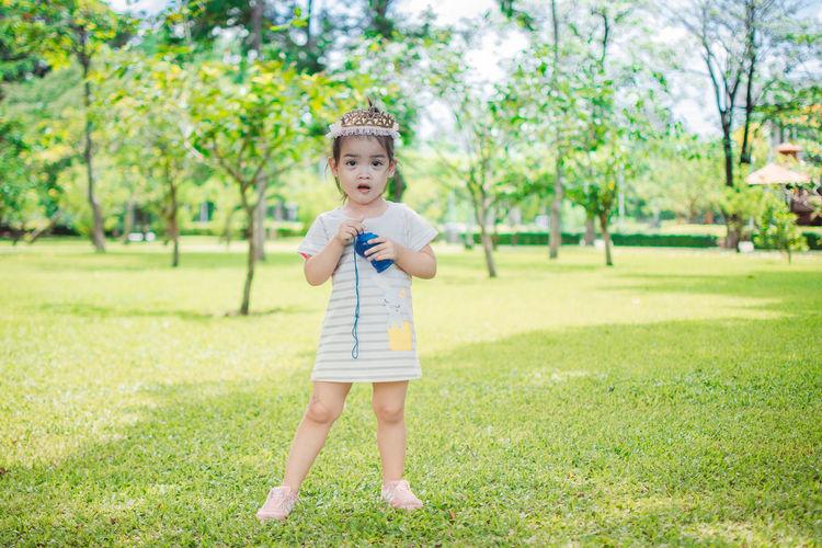 Full length portrait of girl standing at park