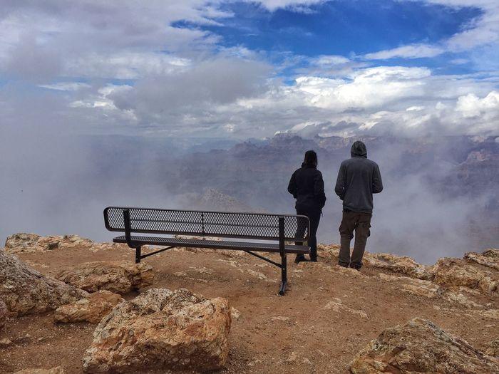Rear View Of Man And Woman Standing On Mountain Against Cloudy Sky