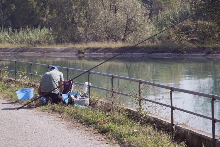 Man with fishing equipment kneeling on bridge over river