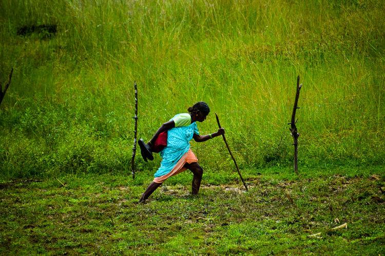 Full length rear view of man holding umbrella on field