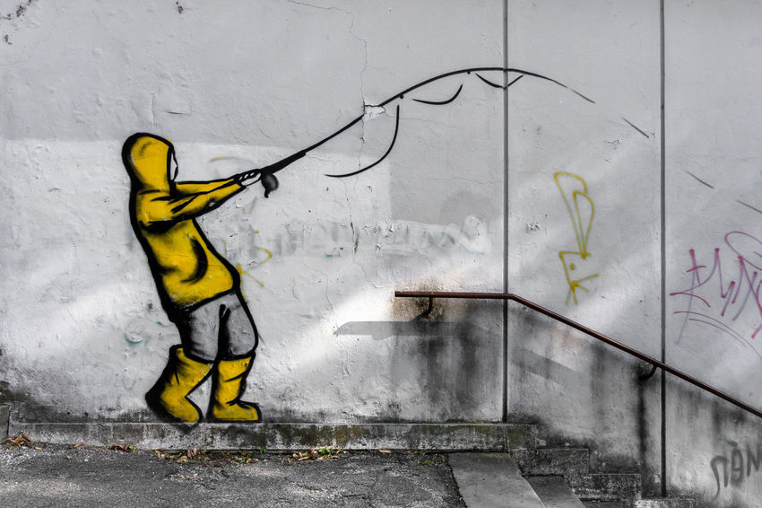 Street art by unknown artist on a concrete wall. The painting represents a boy fishing, suit with raincoat and yellow galoshes. Artist Beautiful Boots City Colors Exterior Graffiti Life Lifestyle Art Boy Building Built Structure Color Colorful Concept Concrete Design Detail Fishing Galoshes Gray Grey Handrail  Outdoor