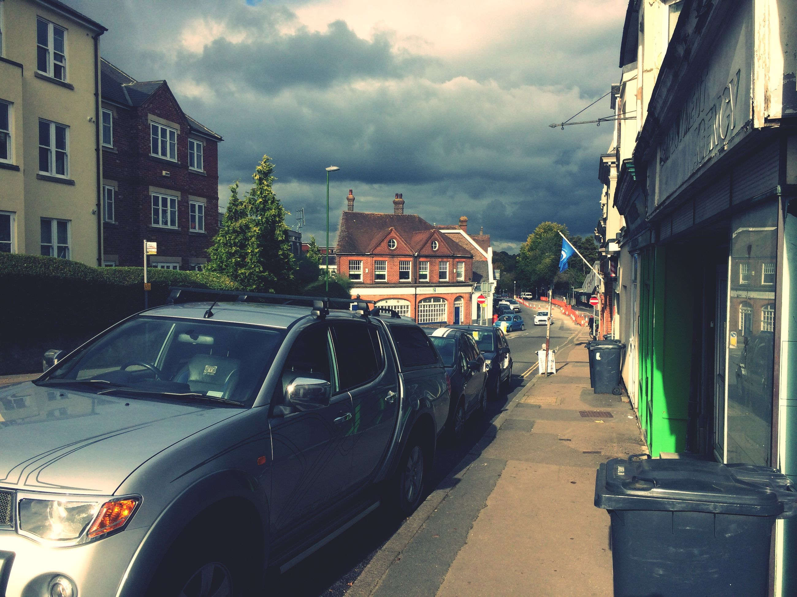 building exterior, architecture, car, transportation, built structure, land vehicle, mode of transport, street, road, city, illuminated, sky, city street, cloud - sky, parking, cloud, city life, stationary, day, storm cloud, tail light, motor vehicle, town
