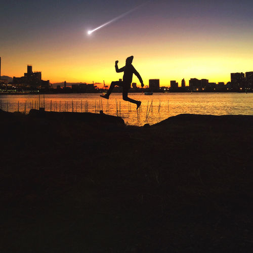 Silhouette Man Jumping On Beach By City Against Shooting Star In Orange Sky