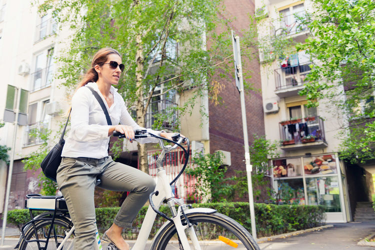 Low angle view of woman riding bicycle on road