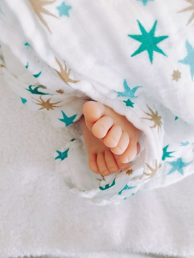 Low section of baby lying down on bed