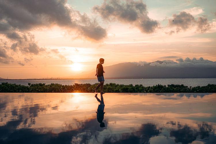 Full length of man standing on shore against sky during sunset
