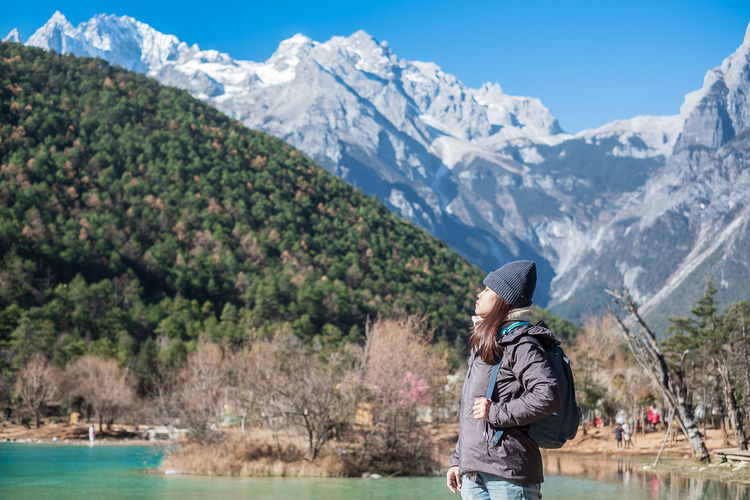 Side view of woman wearing backpack while standing against mountains during winter