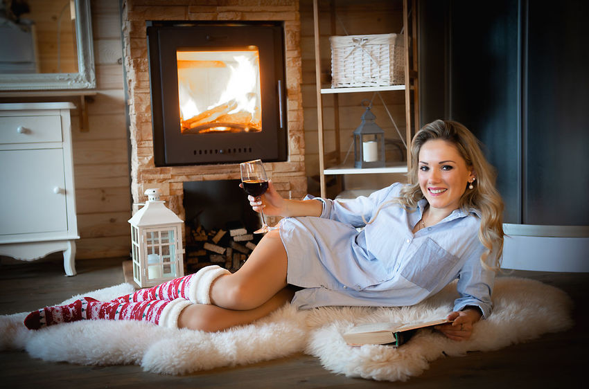 A young beautiful blonde woman relaxing with a glass of wine and a book at the fireplace in a cozy mountain cabin Beautiful Woman Relaxing Cabin Mountain Cabin Cabin Life Rustic Cabin Rustic Style Wine Glass Book Read Book Young Adult One Person Women Lifestyles Relaxation Winter Wintertime Holidays Vacations Christmas Decoration Christmas Socks Celebration Merry Christmas!