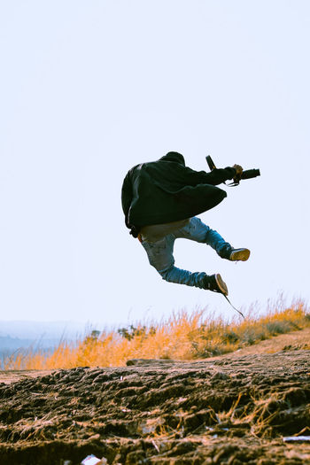 Low angle view of man jumping on field against clear sky