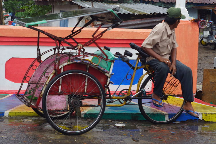 waiting costumer at the traditional market Transportation Bicycle Mode Of Transportation Real People One Person Land Vehicle Men City Casual Clothing Day Occupation Full Length Street Standing Lifestyles Architecture Leisure Activity Rear View Outdoors Riding
