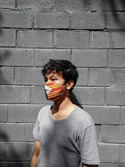 Man wearing mask standing against wall