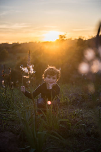 Beauty In Nature Child Childhood Cute Field Flower Grass Innocence Kid Land Leisure Activity Lens Flare Lifestyles Nature One Person Outdoors Plant Real People Selective Focus Sky Smile Sun Sunlight Sunset