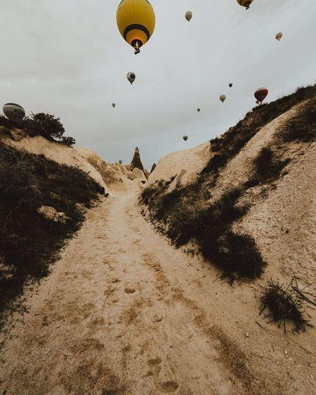 Hot Air Balloon Flying Adventure Sky Mid-air Sand Outdoors Vacations Heat - Temperature Transportation Landscape Sand Dune Parachute Jumping Beach Day Full Length Nature Ballooning Festival People Kapadokya Turkey Cappadocia