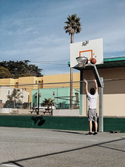 Full Length Of Man Playing Basketball In Court Against Sky
