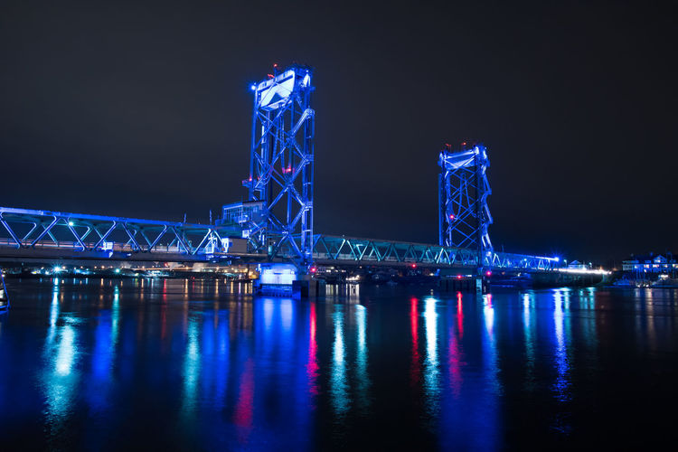 Low angle view of illuminated memorial bridge over river