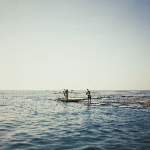People fishing in the sea against clear sky