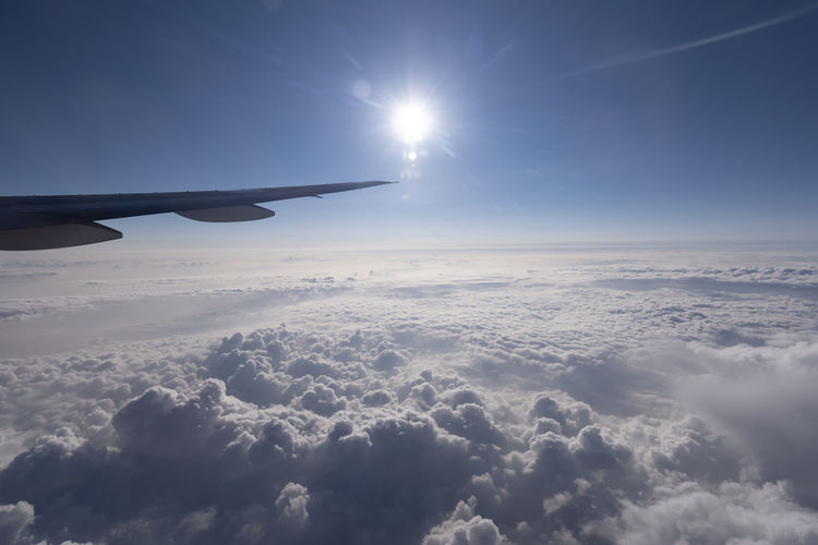 Sky Cloud - Sky Air Vehicle Airplane Beauty In Nature Sun Sunlight Scenics - Nature Nature Aircraft Wing Flying Transportation Mode Of Transportation Cloudscape No People Travel Mid-air Tranquility Aerial View Tranquil Scene Outdoors Lens Flare Meteorology Above